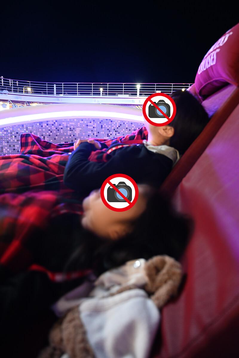 ダイヤモンド・プリンセス 夜のプールチェアで寝そべる妻と娘